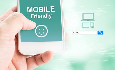 Handaanraking mobiele telefoon met mobiele vriendelijke woord zoekvak wazig blauwe achtergrond, digitale marketing business concept. Stockfoto