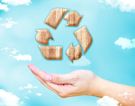 ecological environment: Open female hand with Recycle wood sign icon with blue sky and cloud, Ecology concept. Stock Photo
