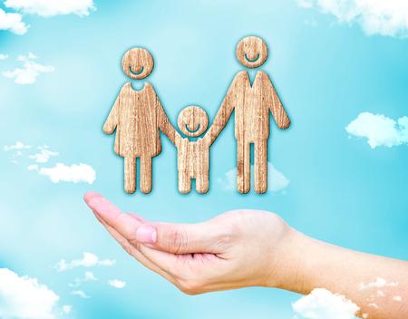 madre e hijo: Abrir la mano femenina con el icono feliz de la familia de madera con el cielo azul y la nube, el concepto de familia.