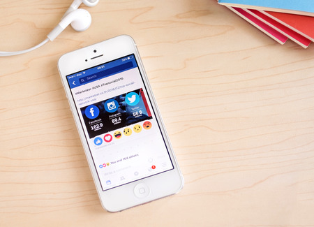 features: Bangkok, Thailand - February 26, 2016: iPhone with New facebook like button (6 emoji) on screen on table ,Social media are using for information sharing and networking