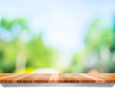 Leere braune Holztischplatte mit Sonne und grünen Baum Hintergrund Bokeh verwischen, verspotten Vorlage für die Montage des Produkts auf.