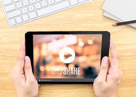 Mano que sostiene la tablilla con el vídeo en pantalla compartir en la mesa de madera, concepto de marketing en Internet