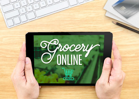 Hand hält Tablette mit Lebensmittel Online Wort auf Holz Tisch, Online-Shopping-Konzept Standard-Bild