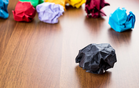 Black crumpled paper ball on dark brown wood table with group of colorful crumpled paper ball at background,Creative idea concept.