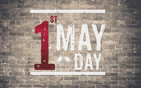 the working day: 1 día de mayo (Día Internacional del Trabajo) en la pared de ladrillo, el concepto de vacaciones.