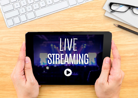live stream tv: Hand holding tablet with Live Streaming word on wood table ,Internet marketing concept..