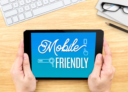 friendly: Hand holding tablet with Mobile friendly word on wood table ,Digital marketing concept