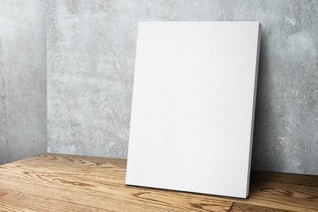 Marco de lienzo blanco en blanco apoyado en la pared de concreto y piso de madera, plantilla de maqueta para agregar su diseño Foto de archivo