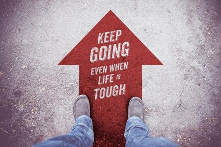 """Inspiration citation: """"Continuez même quand la vie est dure» à la vue aérienne de la chaussure sur la route avec aller de l'avant flèche rouge"""