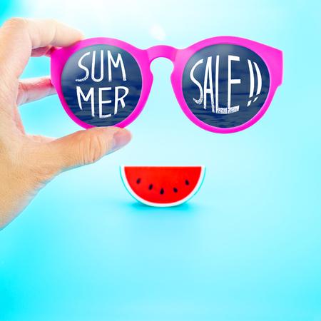 Hand met zomer roze glazen met zomer verkoop! Woord en watermeloen op lichtblauwe achtergrond