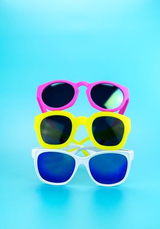 vacation summer: Three colorful sunglasses at light blue studio background