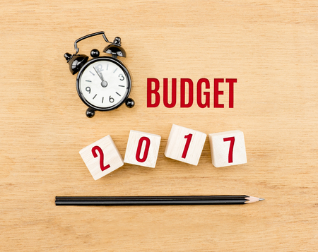 top of the year: Budget 2017 year on wood cube with pencil and clock top view on wood table,New year business concept. Stock Photo