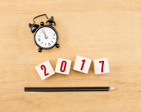 top year: 2017 year on wood cube with pencil and clock top view on wood table,New year business concept.