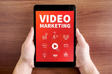 users video: Two hand holding tablet with Video marketing and icon on screen at dark brown table top,Digital business concept.