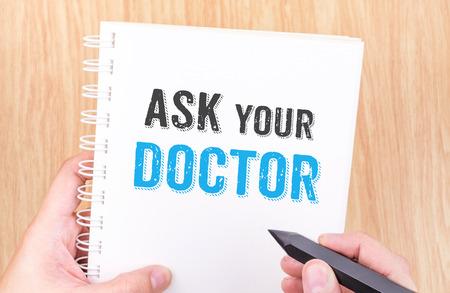 Vraag uw artsenwoord over het witte notitieboekje van het ringsbindmiddel met het potlood van de handholding op houten lijst, het concept van de Gezondheidskaart. Stockfoto