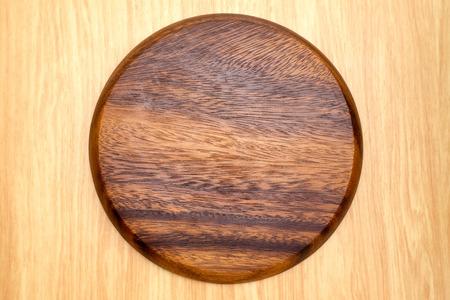 round: Top view of dark brown round wooden chopping block on light wood counter,Kitchenware. Stock Photo