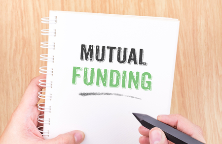financial diversification: mutual funding word on white ring binder notebook with hand holding pencil on wood table,Business concept