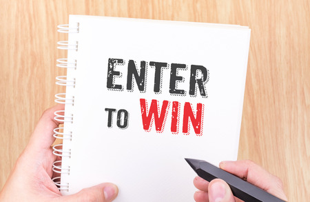 sweepstake: Enter to win word on white ring binder notebook with hand holding pencil on wood table,Game concept.