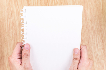 hand paper: Close up Two Hand holding empty white open book above wood desk ,Mock up template for adding your content. Stock Photo