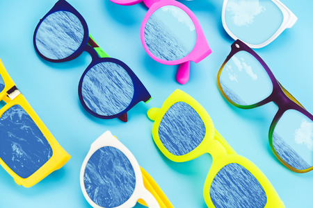 Set of sunglasses lay on blue ground with sea and sky reflection on glass,Summer ,concept,vintage filter.