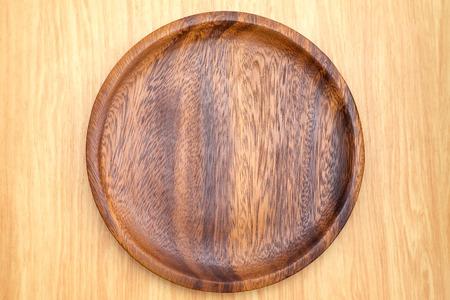 Bovenaanzicht van donkerbruine houten plaat op lichte houten teller, Keukengerei.