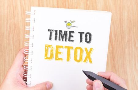 Tijd om woord detox op witte ringbanden laptop met de hand houden potlood op houten tafel, gezonde concept. Stockfoto