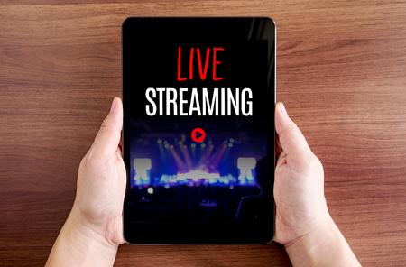 Dwa ręka trzyma tablet z live streaming i ikony odtwarzania na ekranie w ciemnobrązowym blatem, cyfrowe koncepcji. Zdjęcie Seryjne