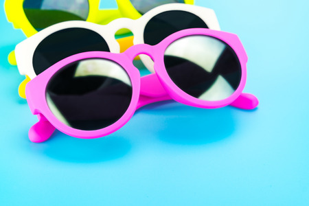 colorful sunglasses at light blue studio background,Summer Holiday concept.