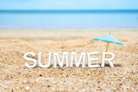 Summer (3D-Rendering Text) weiß Wort mit Sonnenschirm am Sandstrand und blaues Meer Unschärfe Hintergrund, Sommer-Ferien-Konzept. Standard-Bild