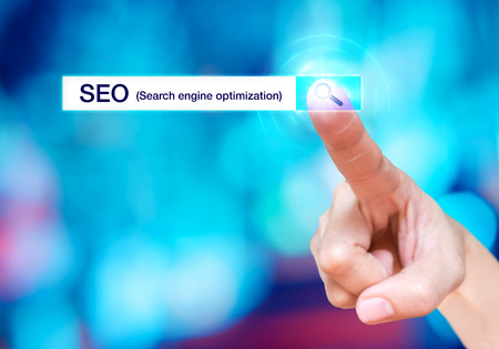 search bar: Finger touch on search button with search bar and SEO (Search engine optimization) word at blur blue background,Digital business concept. Stock Photo