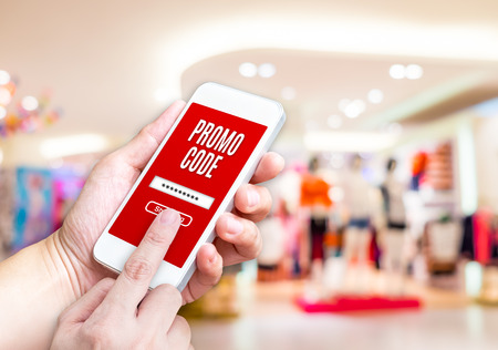 mobile marketing: Hand holding mobile phone with promo code word with blurred store background with bokeh light ,internet marketing concept,E-commerce. Stock Photo