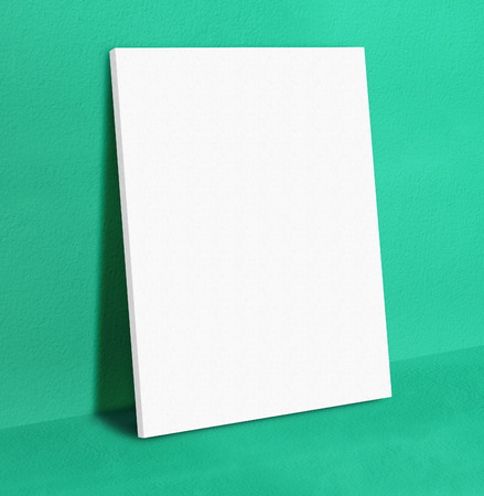 white canvas: Blank white poster canvas frame leaning at green concrete paint wall and floor, Mock up template for adding your design..