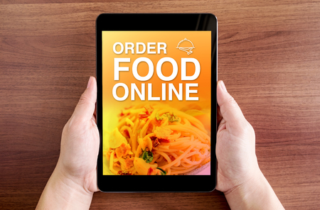 orders: Two hand holding tablet with Order food online and icon on screen at dark brown table top,Digital business concept