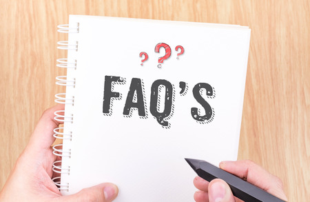 faq's: FAQs word on white ring binder notebook with hand holding pencil on wood table,Business concept.