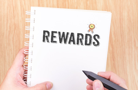 rewarding: Rewards word on white ring binder notebook with hand holding pencil on wood table,Business concept Stock Photo