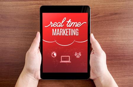 zakelijk: Twee hand die tablet met Real time marketing en het pictogram op het scherm aan donkere bruine tafel top, Digital business concept.