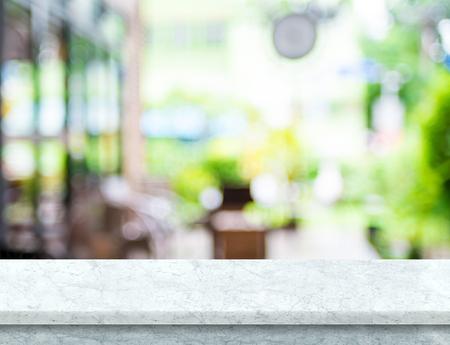 배경에서 정원 나뭇잎 빛 흐림 카페 빈 흰색 대리석 테이블 상단, 표시 또는 제품의 몽타주를 위해 모의. 스톡 콘텐츠