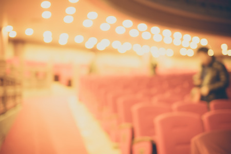 entertainment event: Blurred background, Red seat row in theatre with vintage filter. Stock Photo