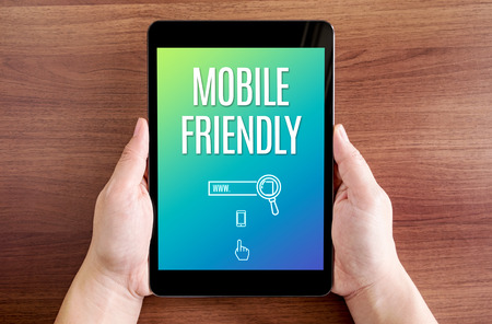 friendly: Two hand holding tablet with mobile friendly and icon on screen at dark brown table top,Digital business concept. Stock Photo
