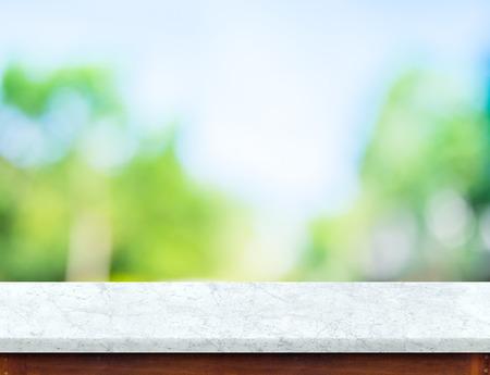 Leere Marmor Tischplatte mit Sonne und verwischen grünen Baum Bokeh Hintergrund, Vorlage Mock up für Montage des Produkts.