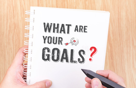 What are your goal? word on white ring binder notebook with hand holding pencil on wood table,Business concept.