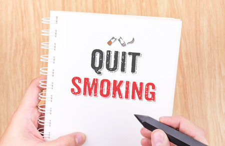 quit smoking: Quit smoking word on white ring binder notebook with hand holding pencil on wood table,Business concept.