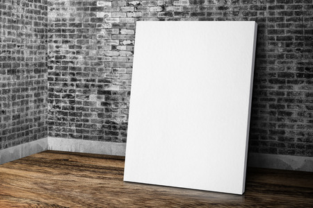 frame wall: Blank white canvas frame leaning at grunge brick wall and wood floor, Mock up template for adding your design
