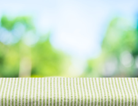 product: Empty green stripes tablecloth with sun and blur green tree bokeh background, Template mock up for montage of product.