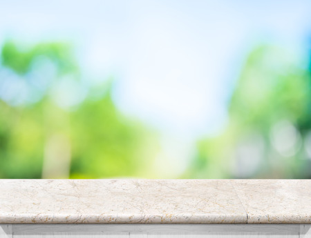 Empty marble table top with sun and blur green tree bokeh background, Template mock up for montage of product.