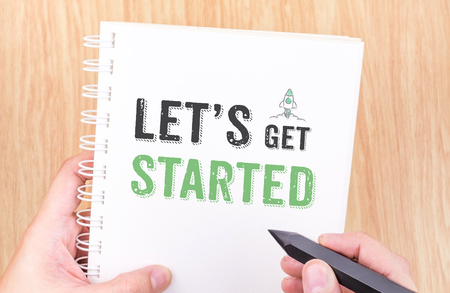 Let's get started word on white ring binder notebook with hand holding pencil on wood table,Business concept.