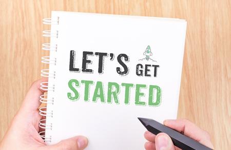 Lassen Sie uns auf weißem Ringbuch Notebook gestartet Wort erhalten mit der Hand hält Bleistift auf Holztisch, Geschäftskonzept. Standard-Bild