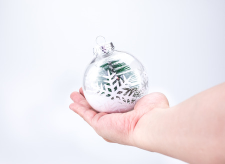hand lay: Christmas decoration light ball with christmas tree inside lay on hand with light grey background,Holiday concept.