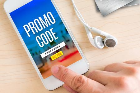Hand berühren Smartphone und Ohrtelefon mit Promo Code-Wort auf Holz Tisch, Internet-Marketing-Konzept. Standard-Bild - 60731571