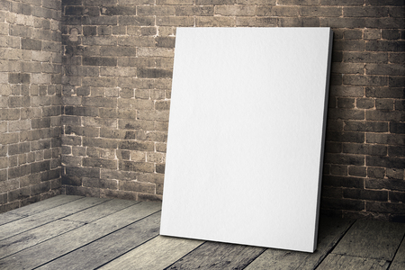 Blank white canvas frame leaning at grunge brick wall and wood floor, Mock up template for adding your design